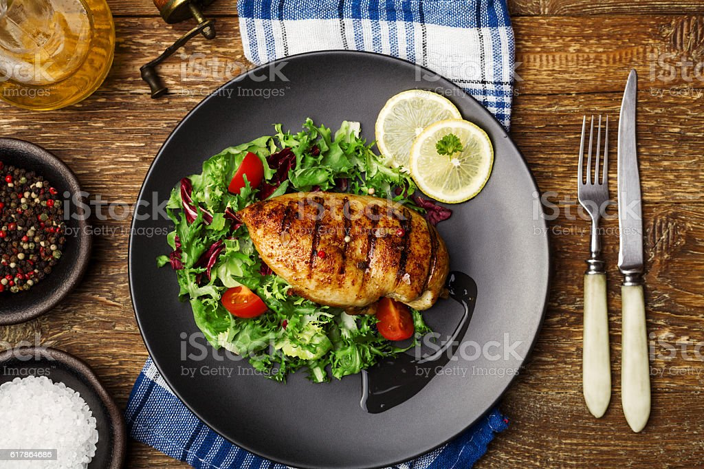 Grilled chicken breast with green salad on a black plate. stock photo