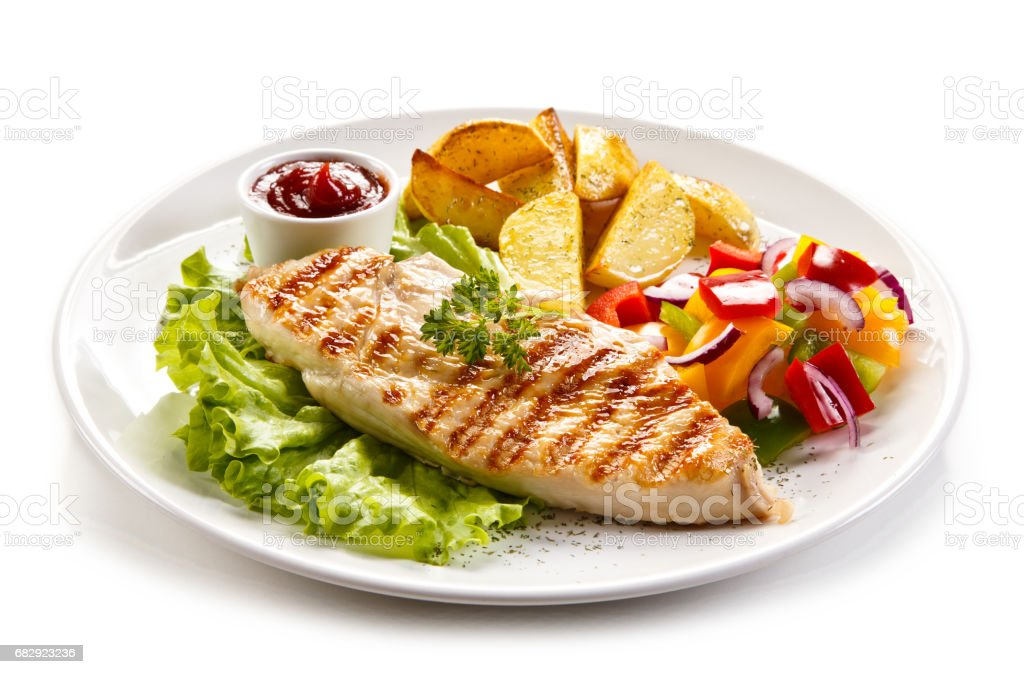 Grilled chicken breast with potatoes and vegetables salad stock photo