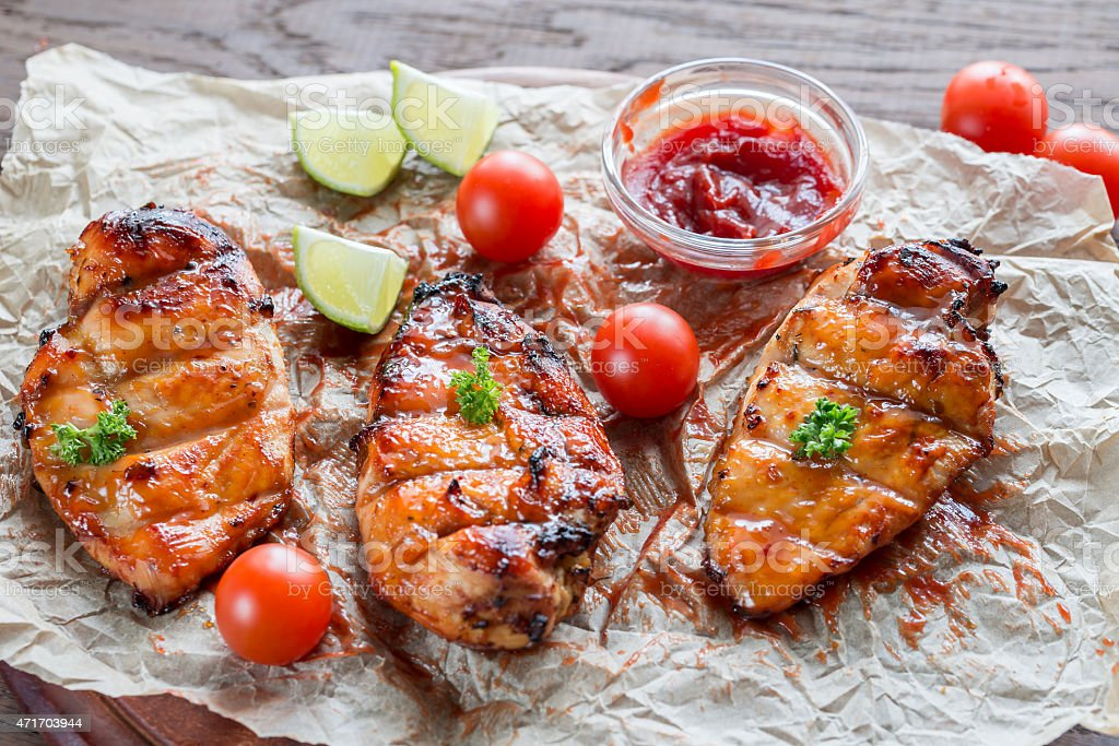 Grilled chicken breasts in hot mango sauce stock photo