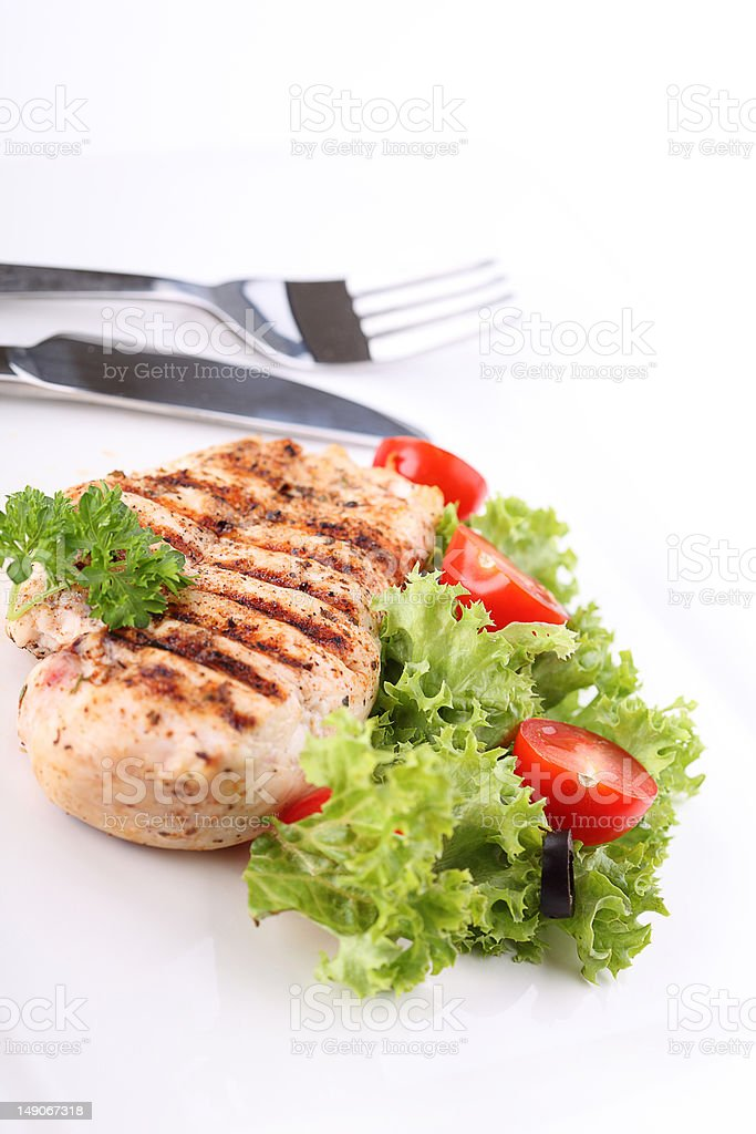 Grilled chicken breasts on a plate with fresh vegetables royalty-free stock photo