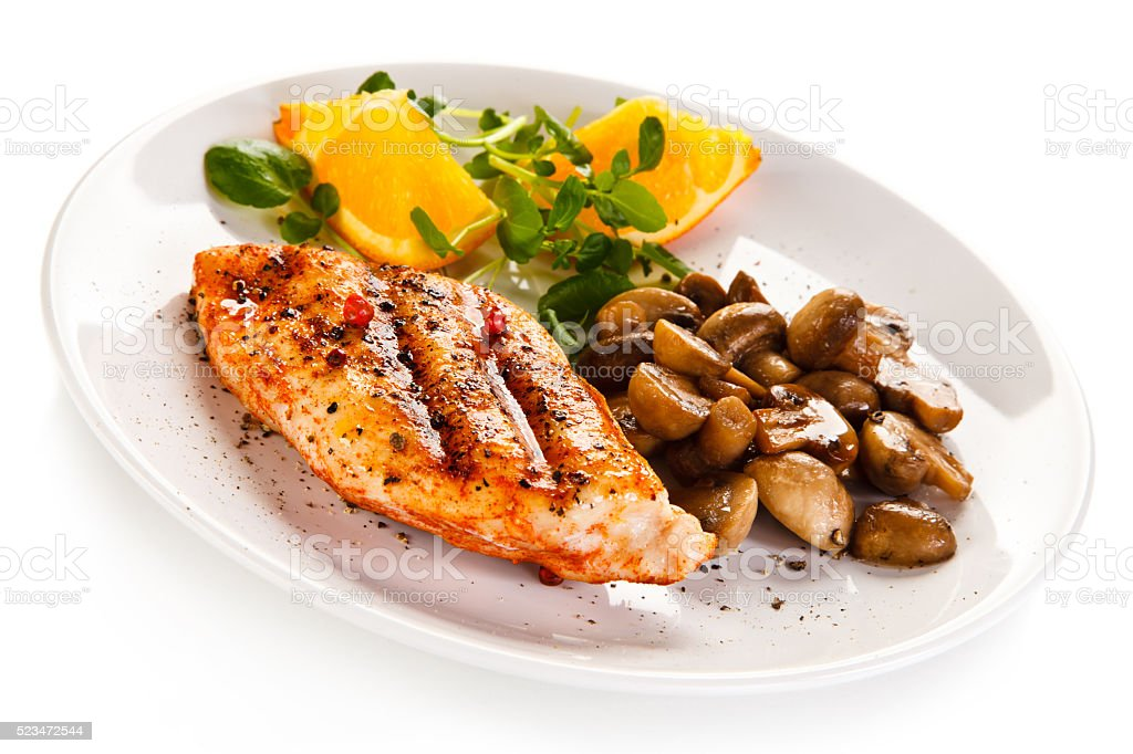 Grilled chicken fillet and fried mushrooms on white background stock photo