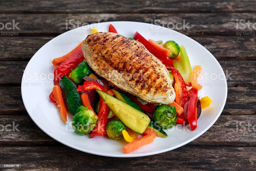 Grilled chicken fillet, breast with cooked vegetable  on plates stock photo