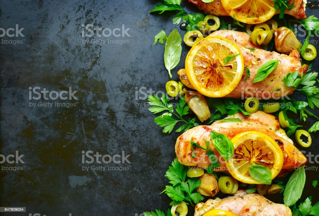Grilled chicken fillet with lemon,green olives and herbs. stock photo