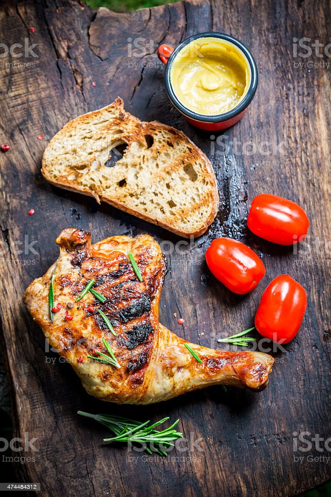 Grilled chicken leg with rosemary and pepper stock photo