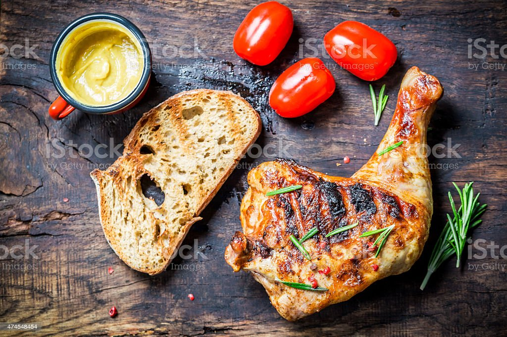 Grilled chicken leg with toast and cherry tomato stock photo