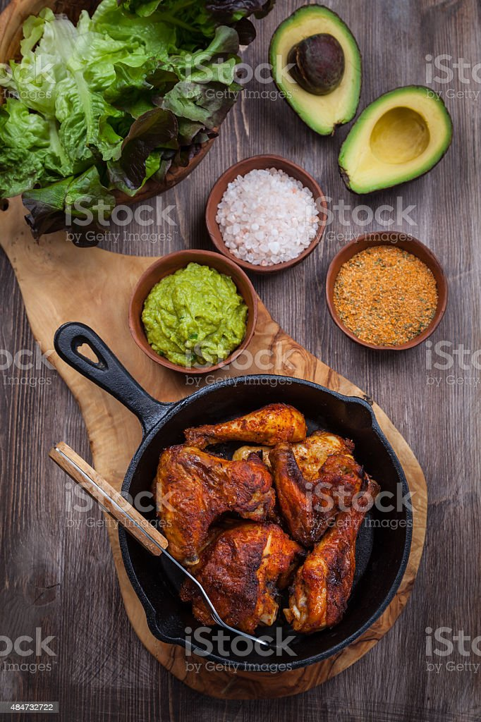 Grilled chicken legs and wings with guacamole stock photo