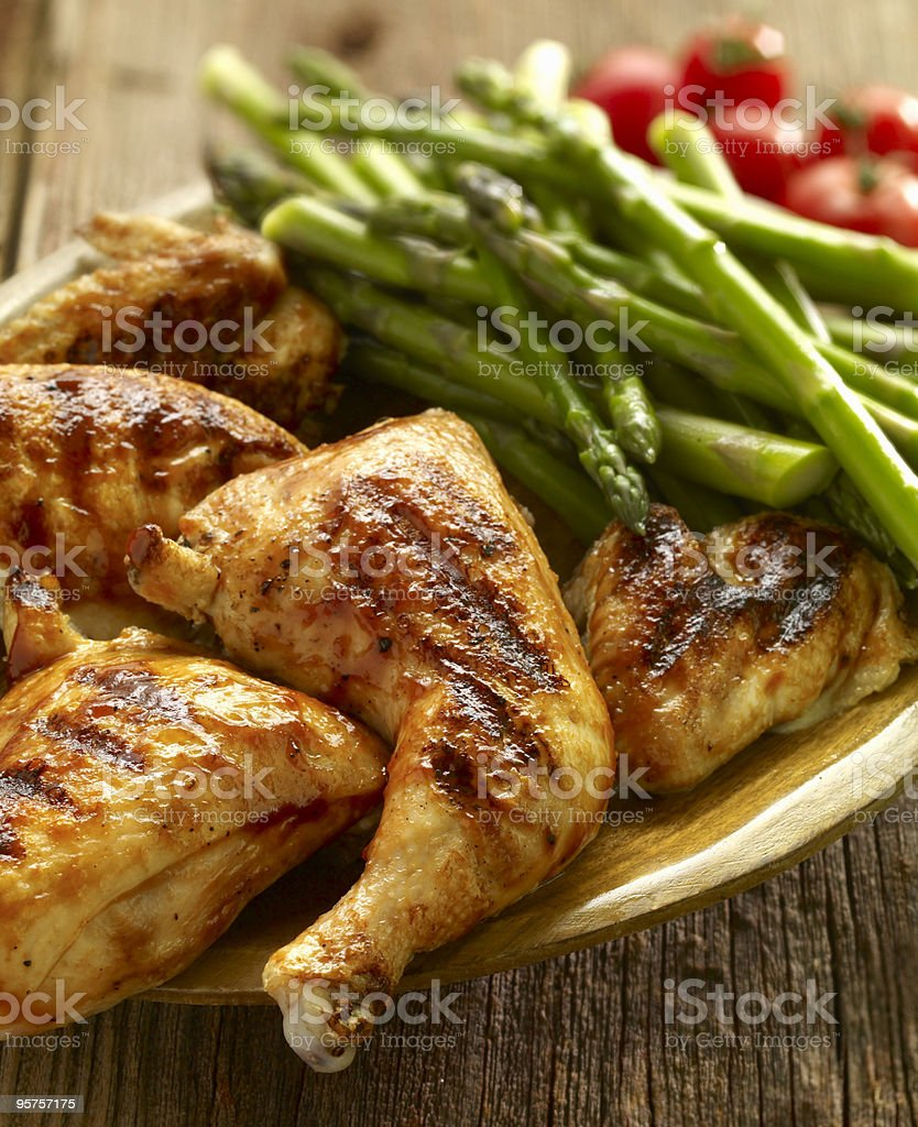 Grilled chicken legs served with asparagus and tomatoes royalty-free stock photo