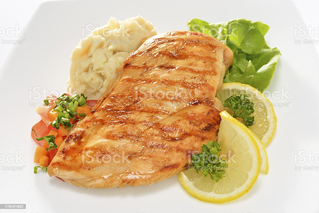 Grilled chicken on plate with mashed potatoes and lemon stock photo
