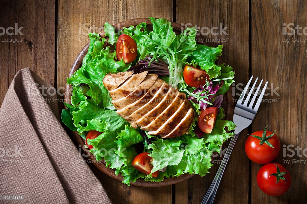 Grilled chicken salad shot from above on rustic wood table stock photo