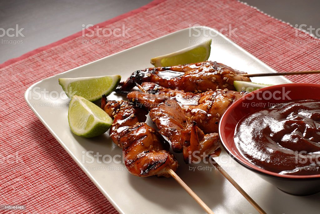 Grilled chicken satay, limes and sauce stock photo