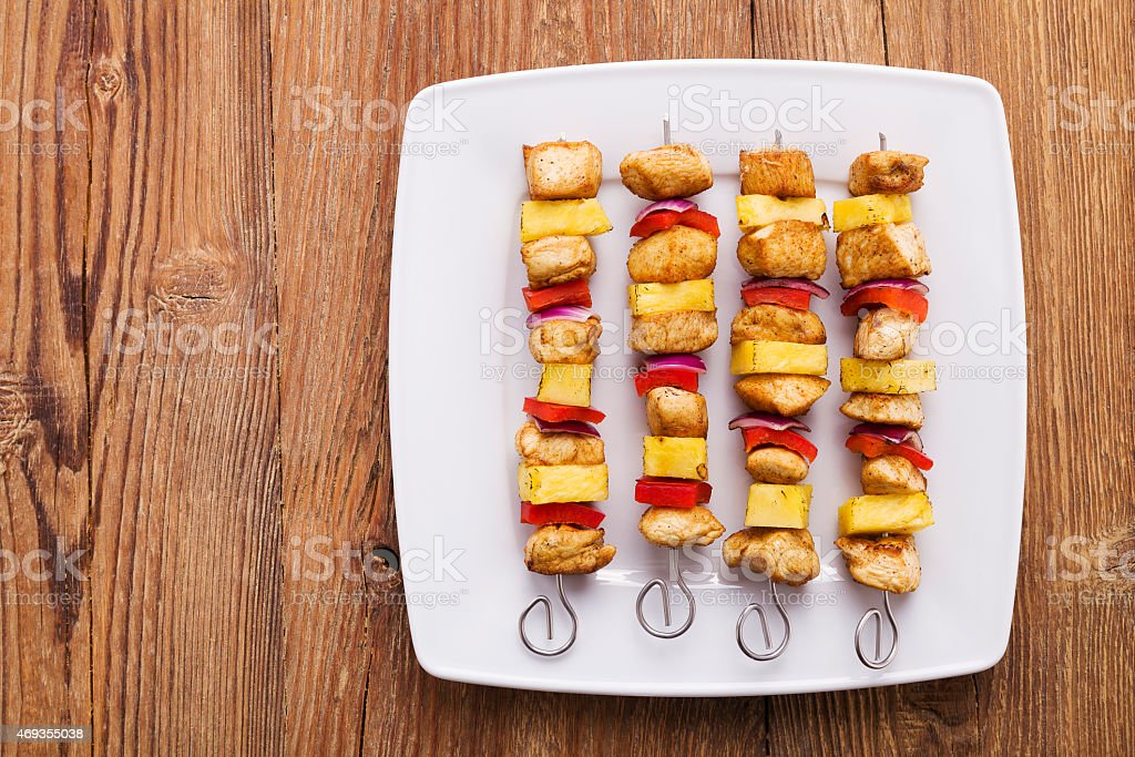 Grilled chicken skewers with pineapple, peppers and onions stock photo