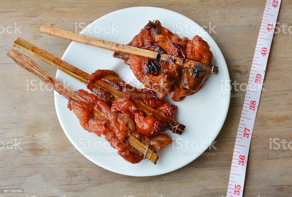 grilled chicken stab in wooden stick and measuring tape stock photo
