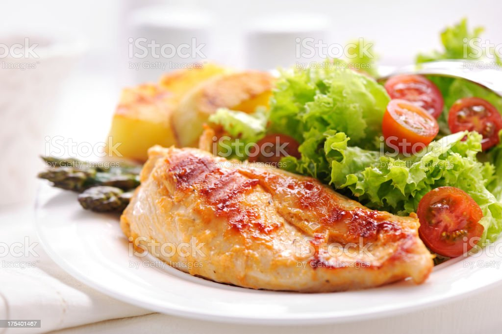 Grilled chicken steak with potatoes,asparagus and salad stock photo