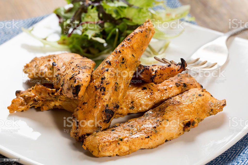 Grilled chicken strips with side salad stock photo