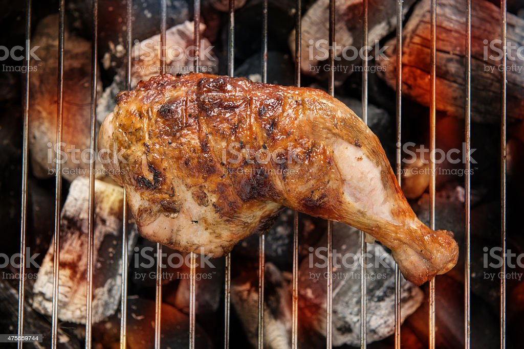 Grilled chicken thigh over flames on a barbecue. stock photo