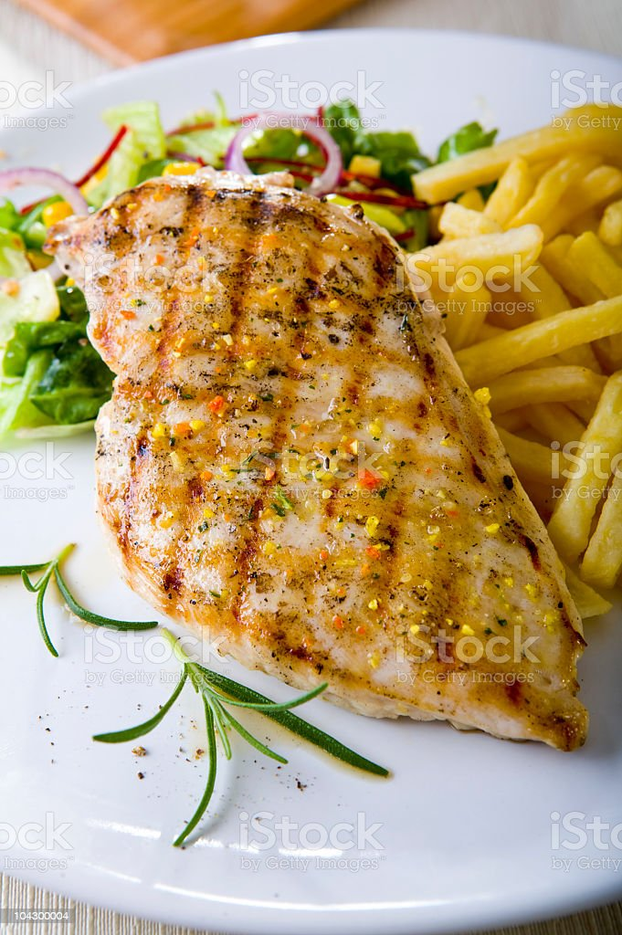 Grilled chicken with chips and salad on white plate royalty-free stock photo