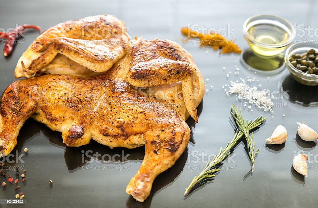 Grilled chicken with ingredients on the dark wooden background stock photo