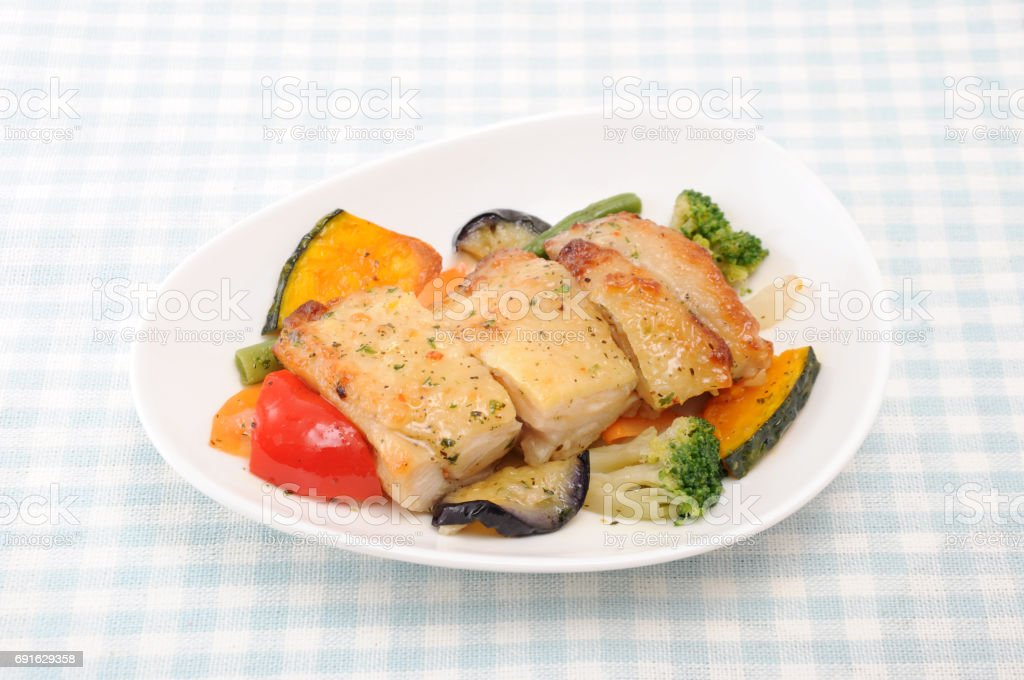 grilled chicken with vegetable on plate on table stock photo