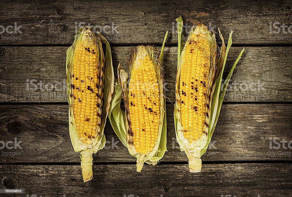 Grilled corn cobs on vintage wood table stock photo