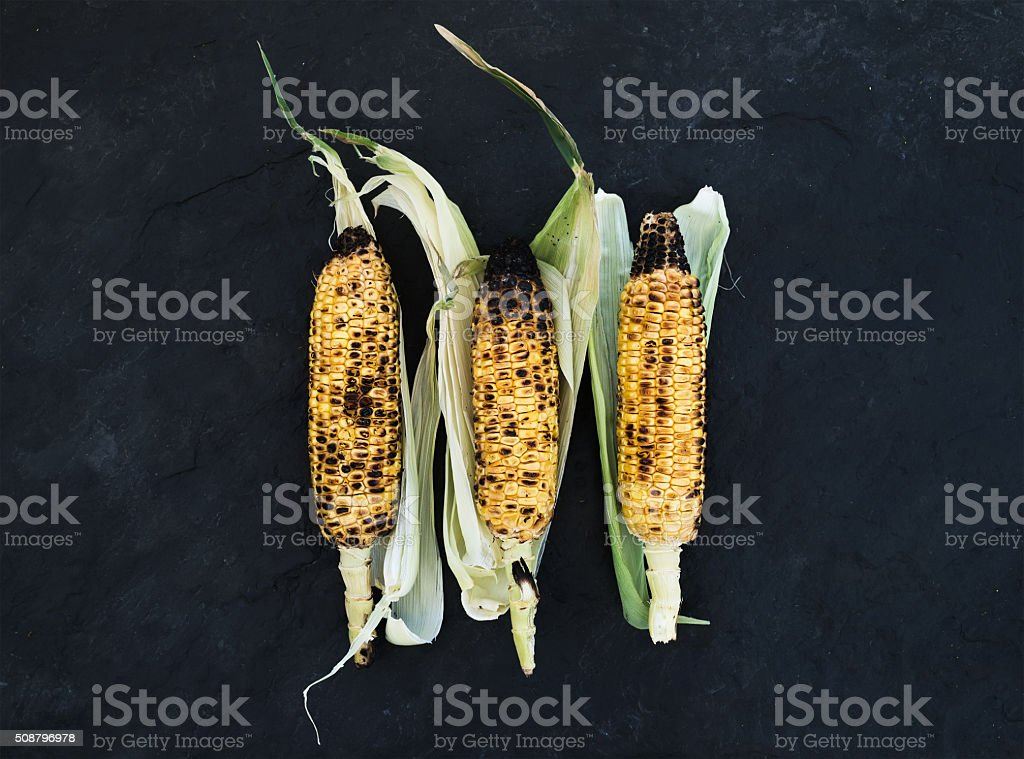 Grilled corn over black slate stone background, top view stock photo