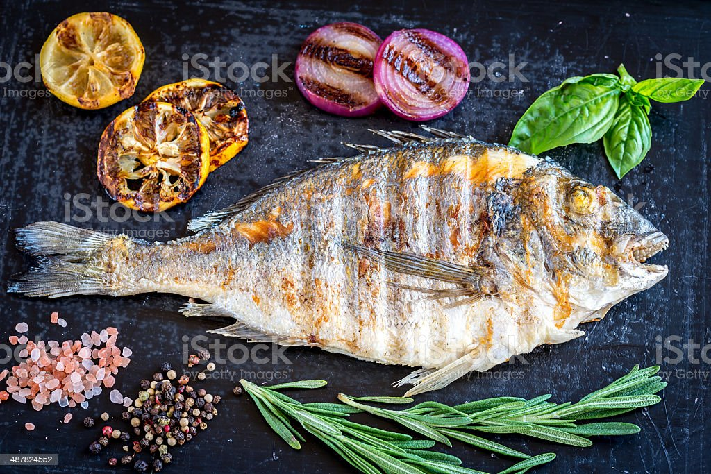 Grilled dorada fish fresh vegetables and herbs stock photo