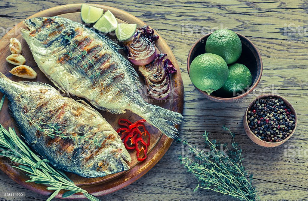 Grilled Dorade Royale Fish on the wooden board stock photo