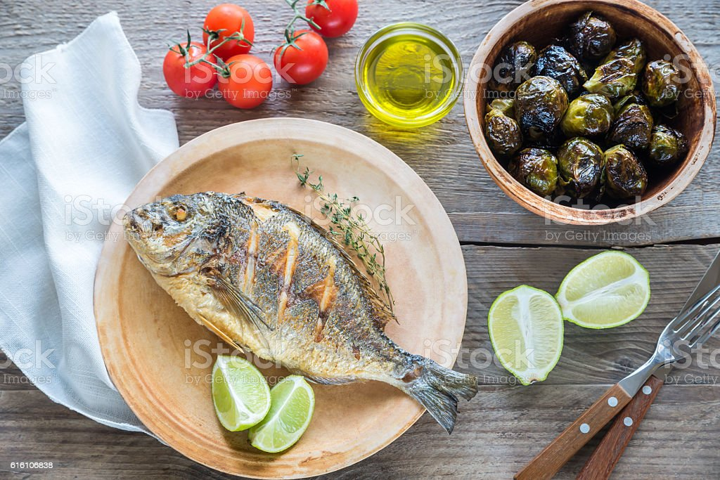 Grilled Dorade Royale Fish with fresh and baked vegetables stock photo