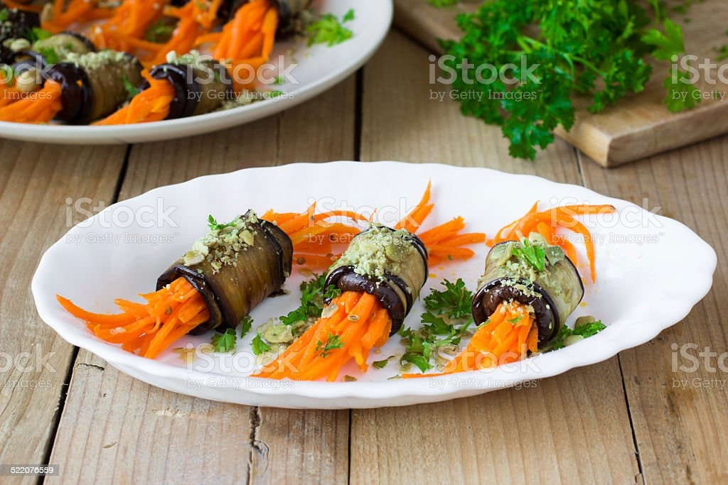 Grilled eggplant rolls with spicy carrot, pumpkin seeds and herbs stock photo