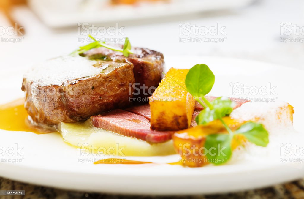 Grilled filet mignon garnished with gourmet sauces and vegetables stock photo