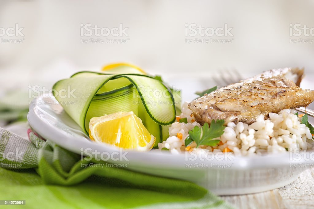 Grilled fillet of herring with zucchini on risotto rice stock photo