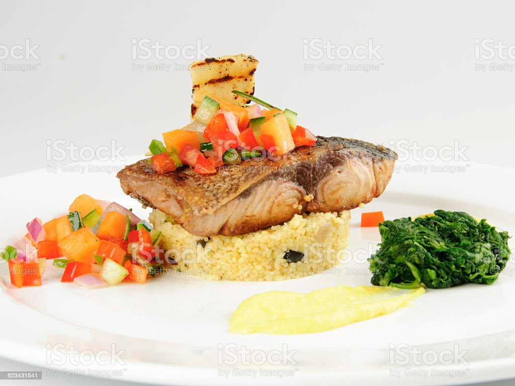 Grilled Fillet of Yellowtail with Papaya & Wilted Greens stock photo