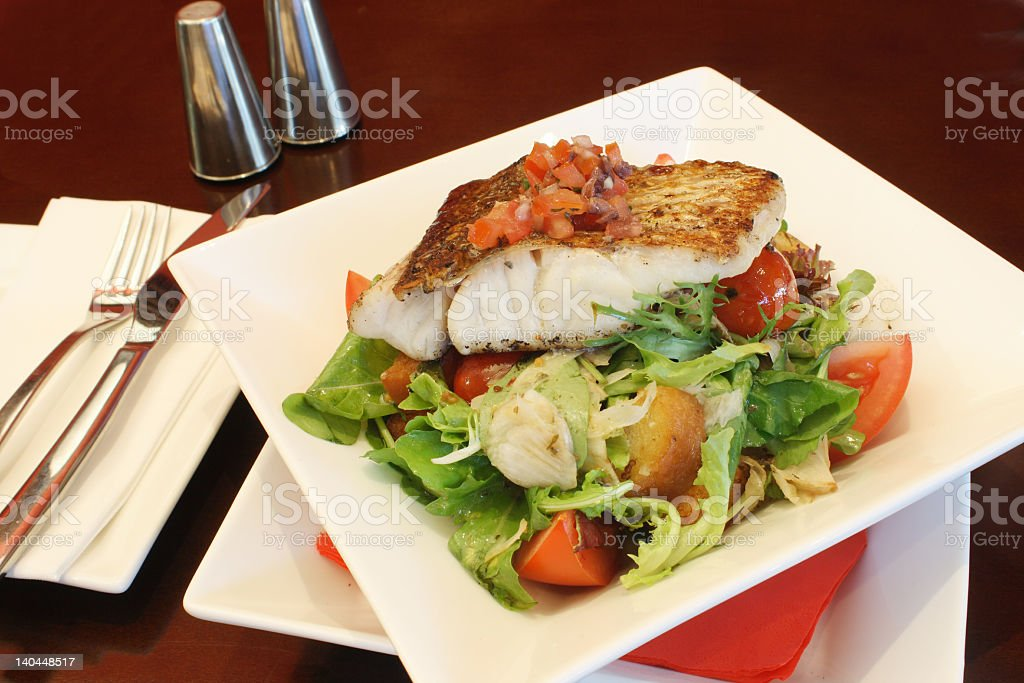 Grilled fish on a plate being served in a restaurant royalty-free stock photo