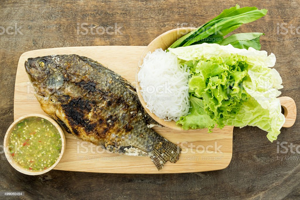 Grilled fish Served on Wooden board with stock photo