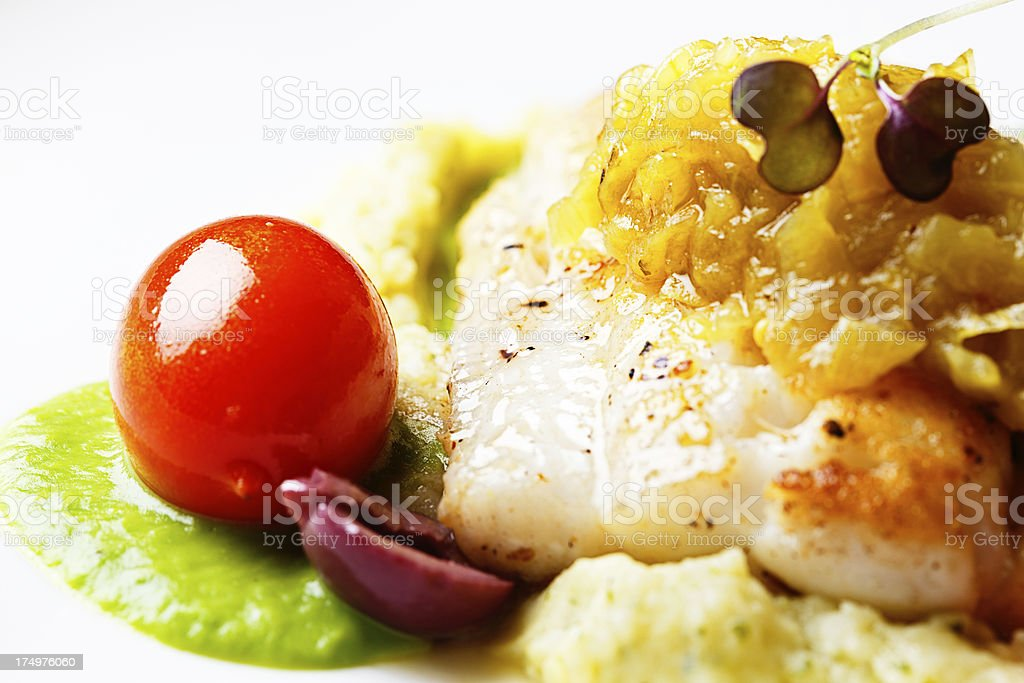 Grilled fish with cherry tomato, lentil puree and micro herbs stock photo