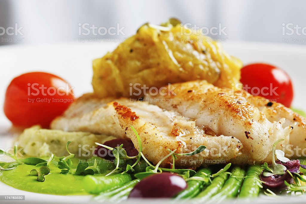 Grilled fish with elegant side dishes in restaurant stock photo