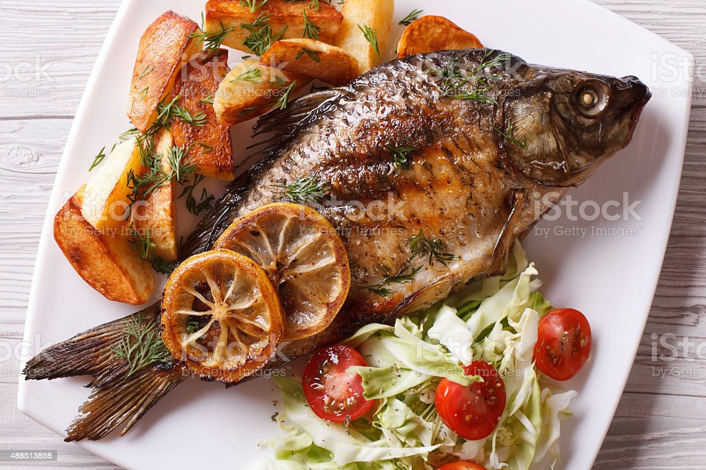 grilled fish with fried potatoes and salad horizontal top view stock photo