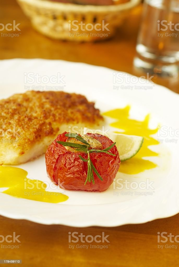 Grilled fish with orange sauce and baked tomato stock photo