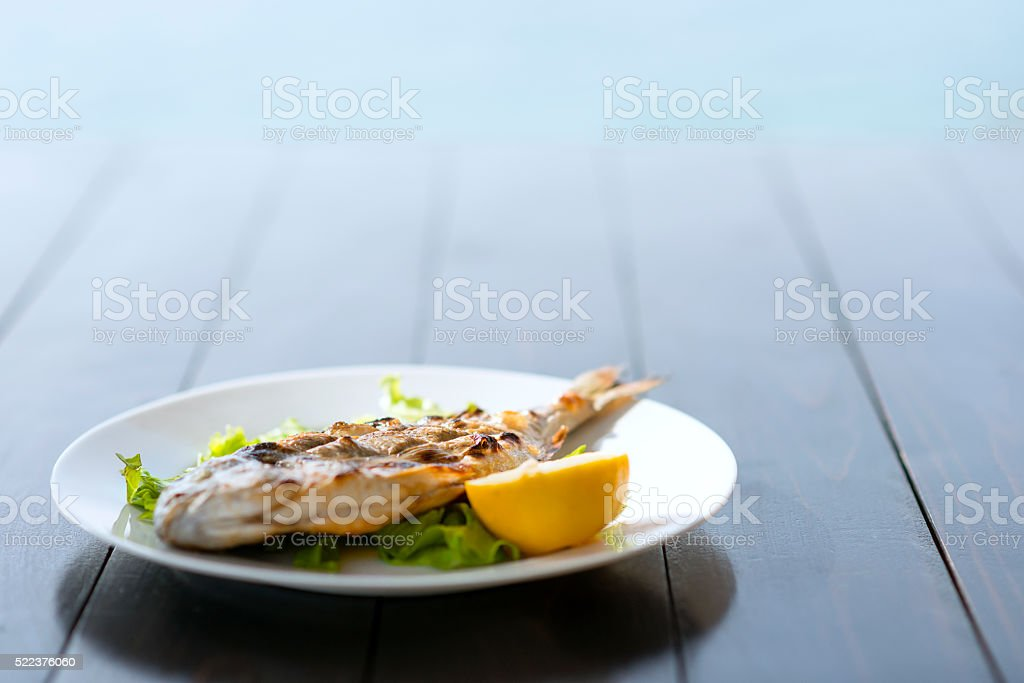 Grilled Fish with Spices and Lemon by the Sea stock photo
