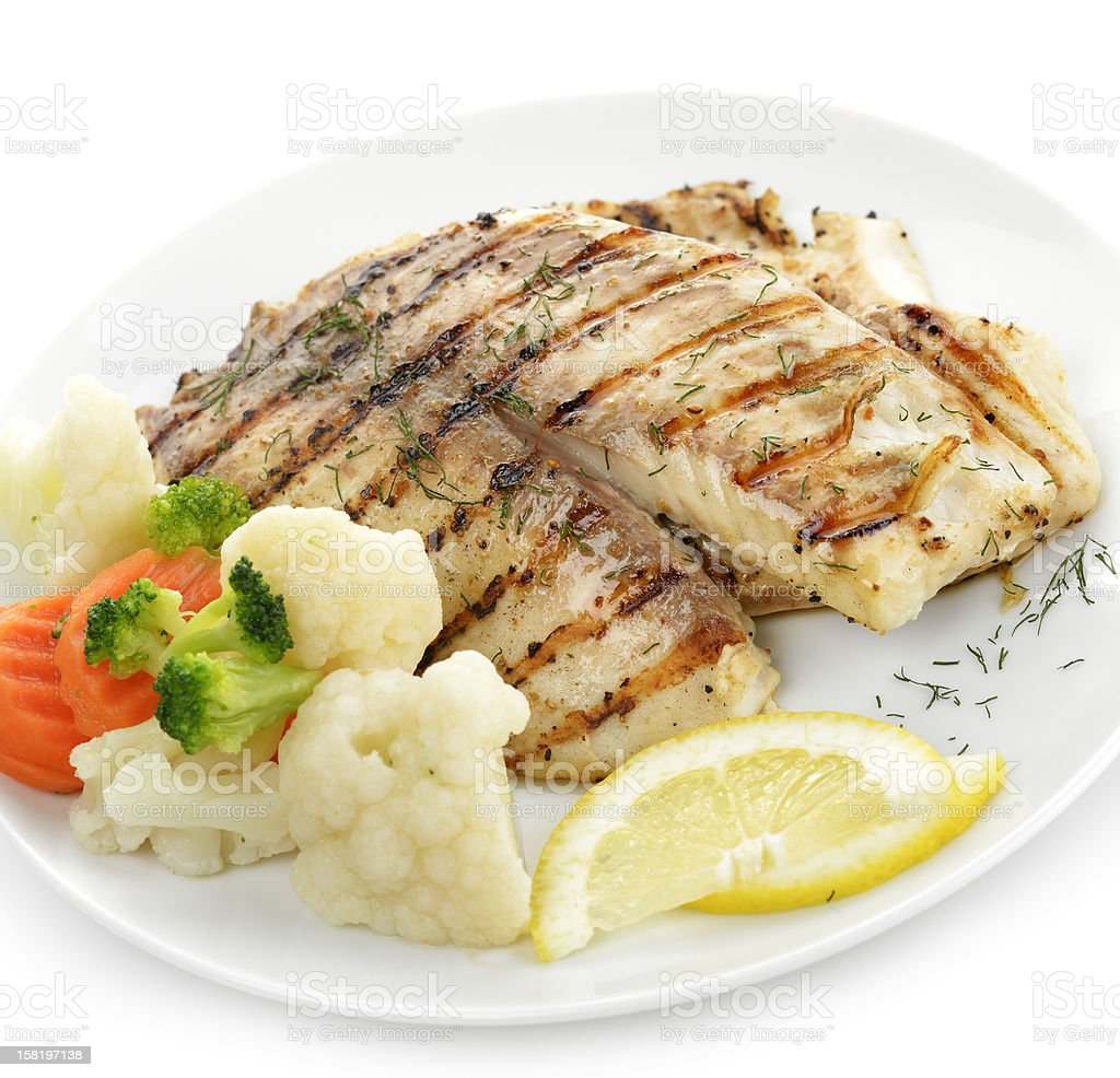 A grilled fresh fish fillet with vegetables and lemon stock photo