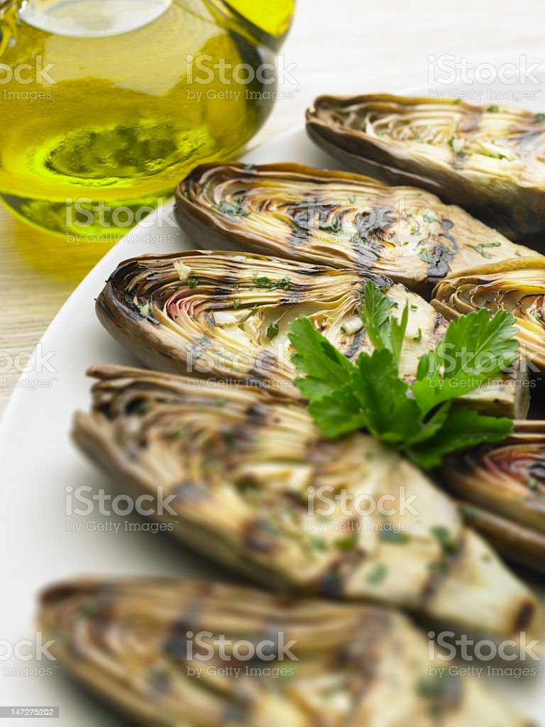 Grilled globe artichokes on a white dish stock photo