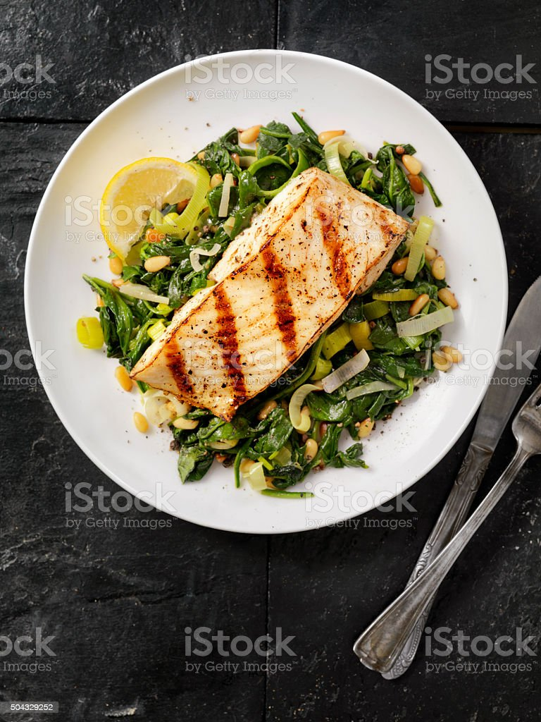 Grilled Halibut with Spinach, leeks and Pine Nuts stock photo
