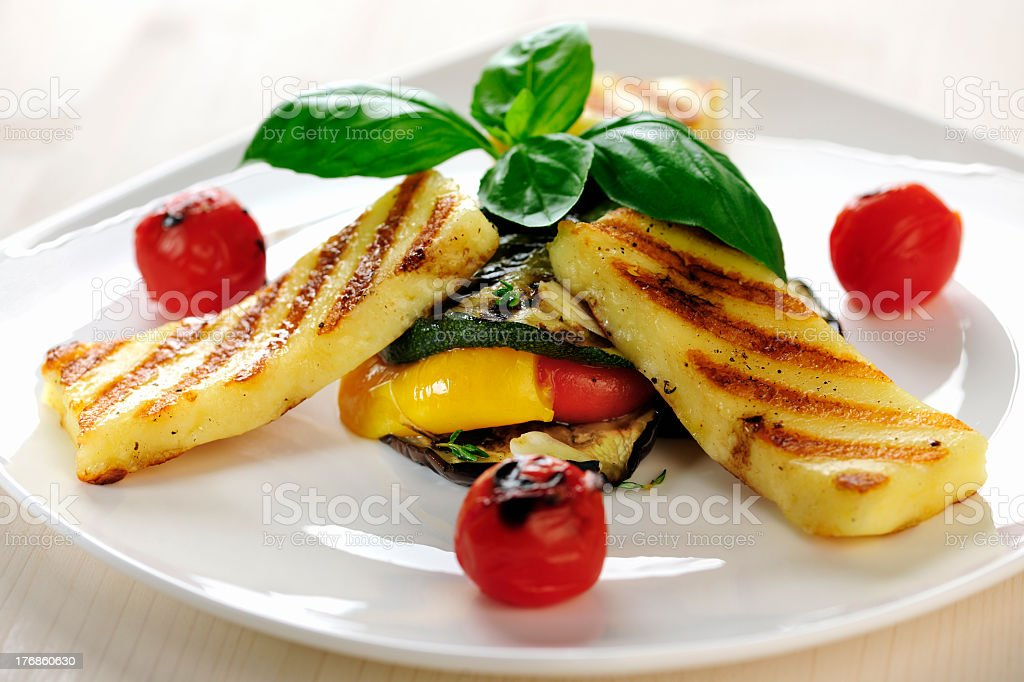 Grilled Halloumi cheese on vegetables with tomato and basil royalty-free stock photo