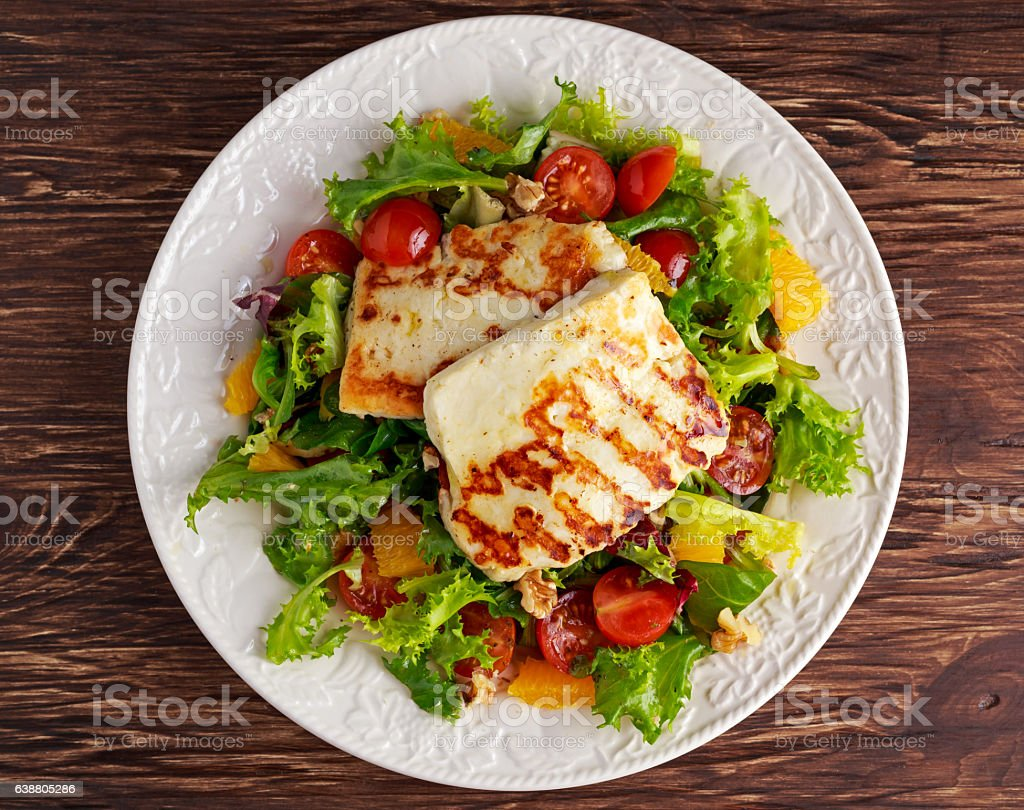 Grilled Halloumi Cheese salad witch orange, tomatoes and lettuce. healthy stock photo