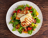 Grilled Halloumi Cheese salad witch orange, tomatoes and lettuce. healthy