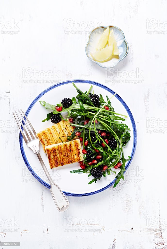 Grilled Halloumi with Blackberry and Arugula Salad stock photo