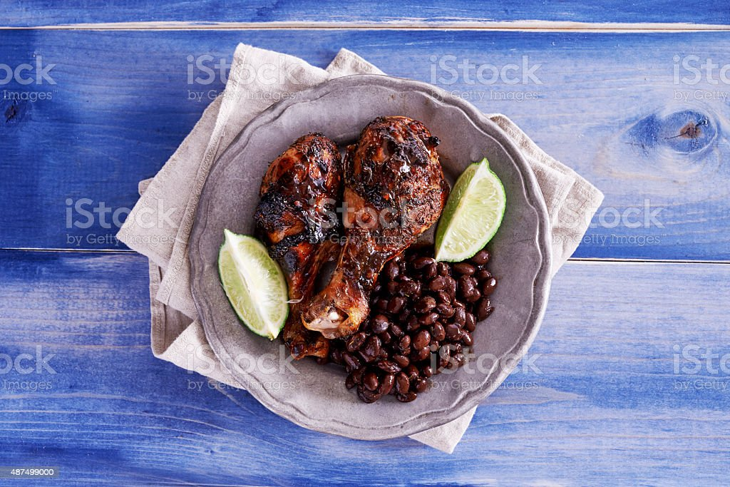 grilled jamaican jerk chicken with black beans shot top down stock photo