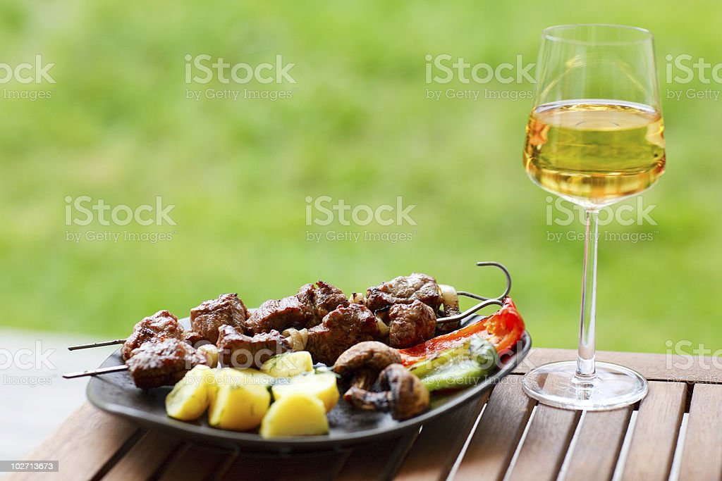 Grilled kebabs on a plate with a glass of wine outdoors royalty-free stock photo