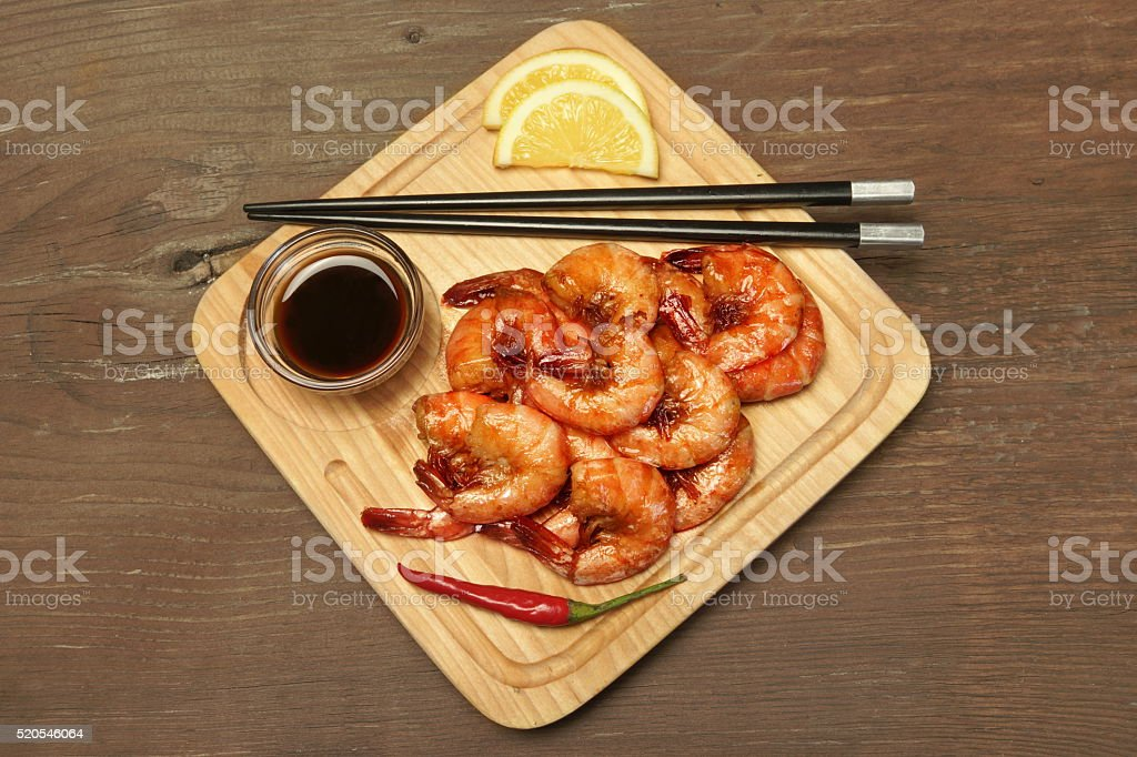 Grilled King Size Shrimps With Sauce Served On Wood Board stock photo