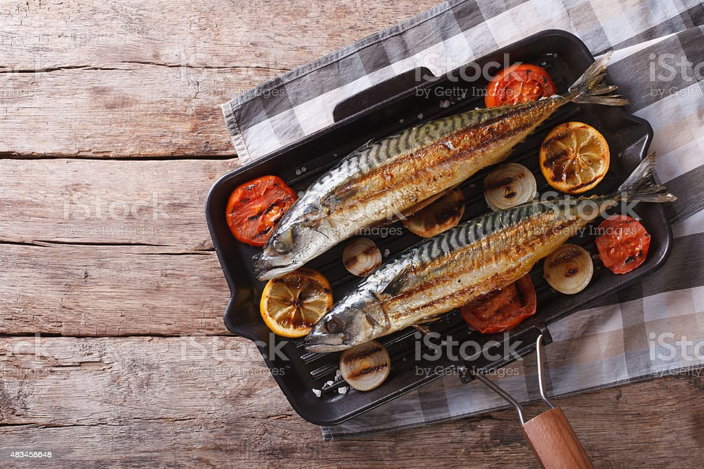 Grilled mackerel in pan with vegetables. horizontal top view stock photo