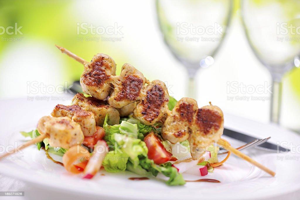 Grilled marinated chicken skewers on raspberry balsamic vinegar salad stock photo